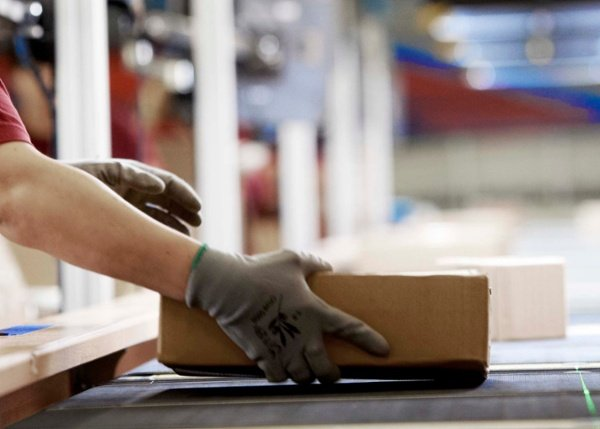 A CEP operator placing a parcel on a conveyor
