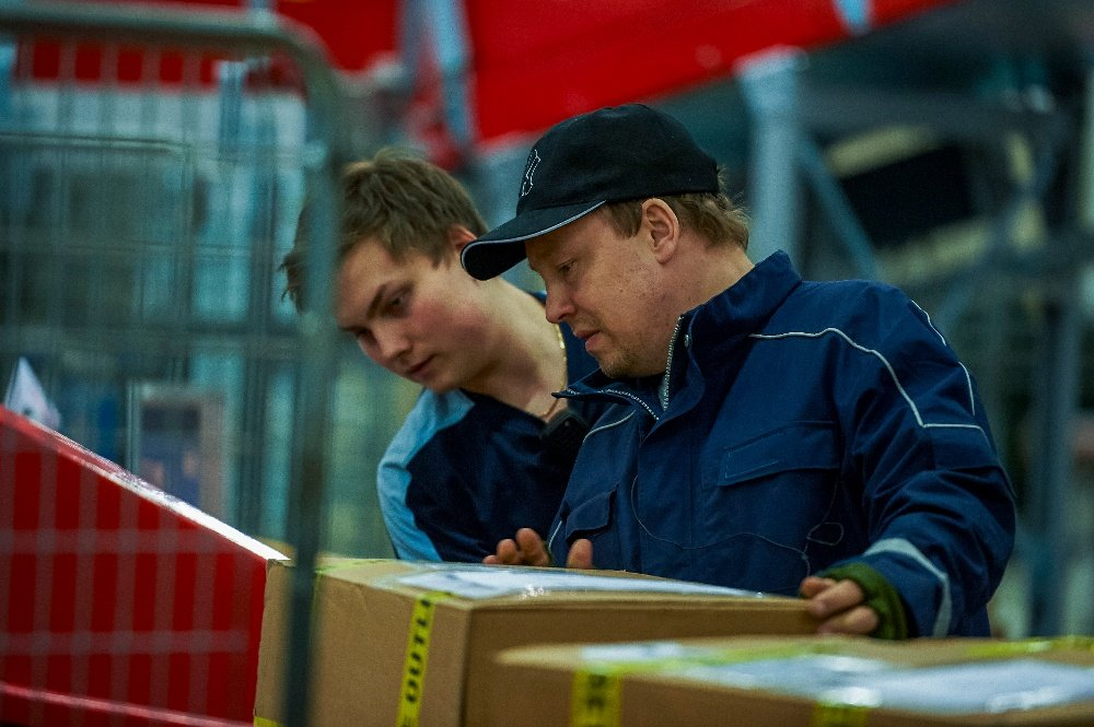 Two CEP operators manually handling parcels.